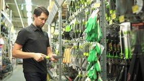 Męska ogrodniczka w narzędzia ogrodniczki sklepowej wybiera małej łopacie zdjęcie wideo