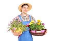 Męska ogrodniczka z słomianego kapeluszu mienia kwiatu roślinami Fotografia Stock