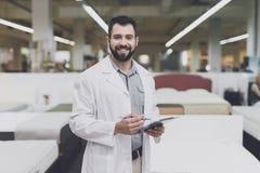 Męska ortopedyczna poza przeciw tłu wielki sklep łóżka Trzyma pastylkę w jego spojrzeniach przy on i rękach Obraz Royalty Free