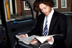 Męska pasażerska czytelnicza gazeta w taxi Obraz Stock