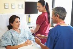Męska pielęgniarka Opowiada Z Żeńskim pacjentem W sala szpitalnej Fotografia Stock