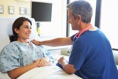 Męska pielęgniarka Opowiada Z Żeńskim pacjentem W sala szpitalnej Zdjęcie Stock