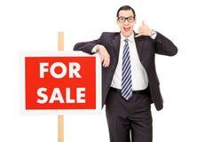 Męska pośrednik handlu nieruchomościami pozycja a dla sprzedaż znaka Fotografia Royalty Free
