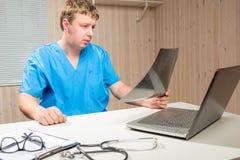 Męska profesjonalista lekarka opisuje promieniowanie rentgenowskie obrazy royalty free