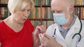 Męska profesjonalista lekarka przy pracą Starszego mężczyzna lekarza fundy starsza żeńska cierpliwa daje grypowa pigułka zbiory wideo