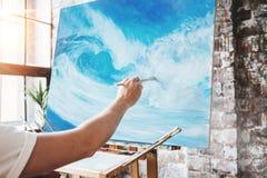 Męska ręka artysty zbliżenia mienia paintbrush na tle kanwa na sztaludze Malarza oceanu rysunkowa fala w studiu Zdjęcia Stock