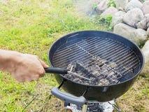Męska ręka czyści sztywniaka round szczotkarskiego grilla przed gotować zdjęcie royalty free