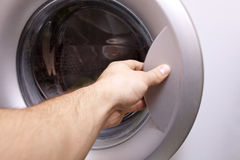 Męska ręka otwiera pralkę 2 Obrazy Stock