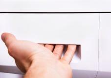 Męska ręka otwiera przedział w pralce dla proszka Zdjęcia Stock