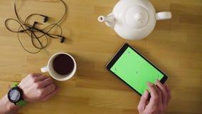 Męska ręka scrolling pastylkę z zieleń ekranem zbiory