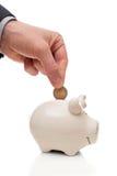 Męska ręka stawia monetę w prosiątko banka Zdjęcia Royalty Free
