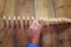Męska ręka stoping domino skutek retro stylowy wizerunku kierownictwo i ryzyka kontrolny pojęcie Zdjęcie Stock