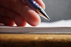 Męska ręka trzyma błękitnego biurowego pióro i pisze biały prążkowany notepad jako symbol brać notatki lub komunikację biznesową Obrazy Stock