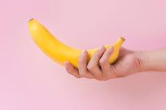 Męska ręka trzyma banana odizolowywający na różowym tle Obraz Royalty Free