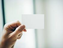 Męska ręka trzyma białą wizytówkę na obraz royalty free