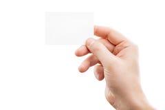 Męska ręka trzyma białą wizytówkę przy odosobnionym tłem Fotografia Stock