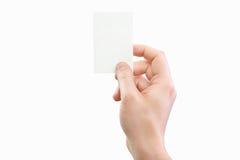 Męska ręka trzyma białą wizytówkę przy odosobnionym tłem Zdjęcia Stock