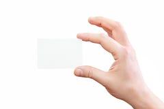 Męska ręka trzyma białą wizytówkę przy odosobnionym tłem Obrazy Stock