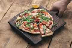 Męska ręka trzyma drewnianą deskę z Włoską pizzą Obrazy Stock