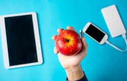 Męska ręka trzyma jabłka z pastylką i telefonem komórkowym Zdjęcie Royalty Free