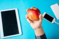 Męska ręka trzyma jabłka z pastylką i telefonem komórkowym Obrazy Stock