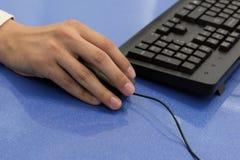 Męska ręka trzyma myszy obok klawiatury Zako?czenie Kierownik lub urzędnik pracujemy na komputerze niebieska t?a obrazy stock