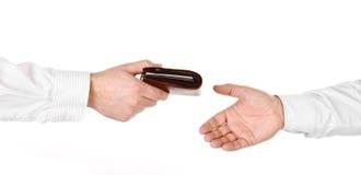 Męska ręka trzyma portfel i wręcza je inna osoba obrazy stock