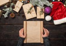 Męska ręka trzyma pustego prześcieradło papier na drewnianym stole Zdjęcia Royalty Free