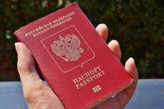 Męska ręka trzyma Rosyjskiego paszport z podpisu paszportem i federaci rosyjskiej w Cyrillic abecadle Zdjęcia Stock