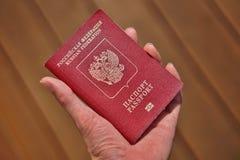 Męska ręka trzyma Rosyjskiego paszport z podpisu paszportem i federaci rosyjskiej w Cyrillic abecadle Obrazy Stock