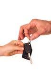 Męska ręka trzyma samochodowego klucz i wręcza je inna osoba Obrazy Stock