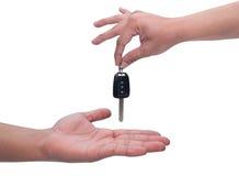 Męska ręka trzyma samochodowego klucz i wręcza je inny perso obraz royalty free