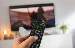 Męska ręka trzyma TV pilot do tv tv i zegarek Obrazy Royalty Free