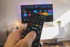 Męska ręka trzyma TV pilot do tv, punktu widzenia strzał Fotografia Stock