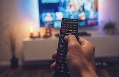 Męska ręka trzyma TV pilot do tv Punktu widzenia strzał Obraz Royalty Free