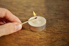 Męska ręka trzyma zapalającego zbawczego dopasowania kij przed zapalać białą świeczkę zdjęcie royalty free