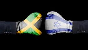 Męska ręka w Bokserskich rękawiczkach z Jamajka i Izrael flaga Jamajka versus Izrael pojęcie fotografia stock