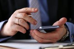 Męska ręka w kostiumu chwyta srebra i telefonu piórze przy miejsca pracy zbliżeniem obrazy stock