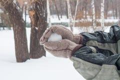 Męska ręka w mitynkach trzymać śnieg w ręce Obraz Stock