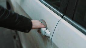 Męska ręka w skórzanej kurtce ciągnie biały samochód zamykającą drzwiową rękojeść zdjęcie wideo