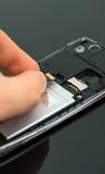 Męska ręka wkłada mikro SD kartę Zdjęcie Stock