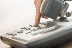 Męska ręka wybiera numer klasycznego kabla naziemnego telefon Obrazy Stock