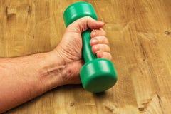 Męska ręka z dumbbells na drewnianej powierzchni Zdjęcie Royalty Free