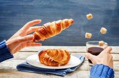 Męska ręka z latającym croissant i kawą Zdjęcia Stock