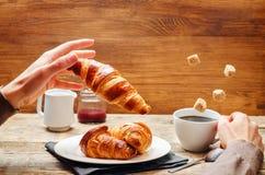 Męska ręka z latającym croissant i kawą Zdjęcie Stock