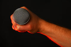 Męska ręka z mikrofonem i czerwonym światłem na czerni Zdjęcia Stock