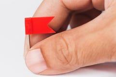 Męska ręka z plastikową czerwonej flaga szpilką Zdjęcie Royalty Free