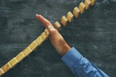 Męska ręka zatrzymuje domino skutek kierownictwo i ryzyka kontrolny pojęcie Fotografia Royalty Free