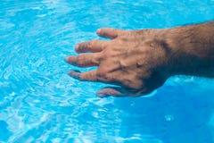 Męska ręki macania jasnego pływackiego basenu woda Fotografia Stock
