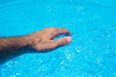 Męska ręki macania jasnego pływackiego basenu woda Obrazy Royalty Free